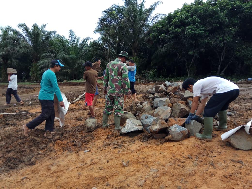 Satgas TMMD Bersama Warga Bergotong Royong Angkut Batu Belah Ke Sekitar Bibir Embung