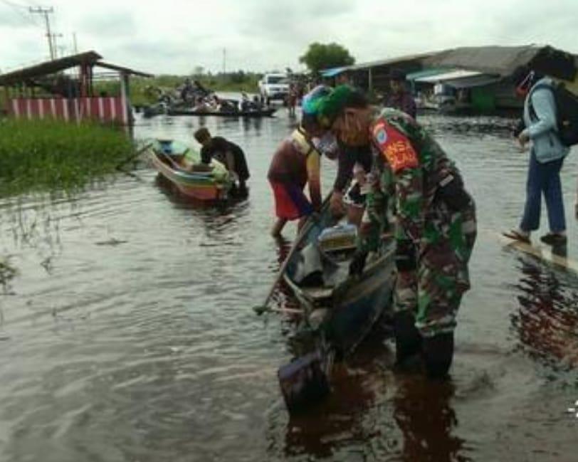 Danramil Bantu warga yang melintasi jalan terendam banjir.