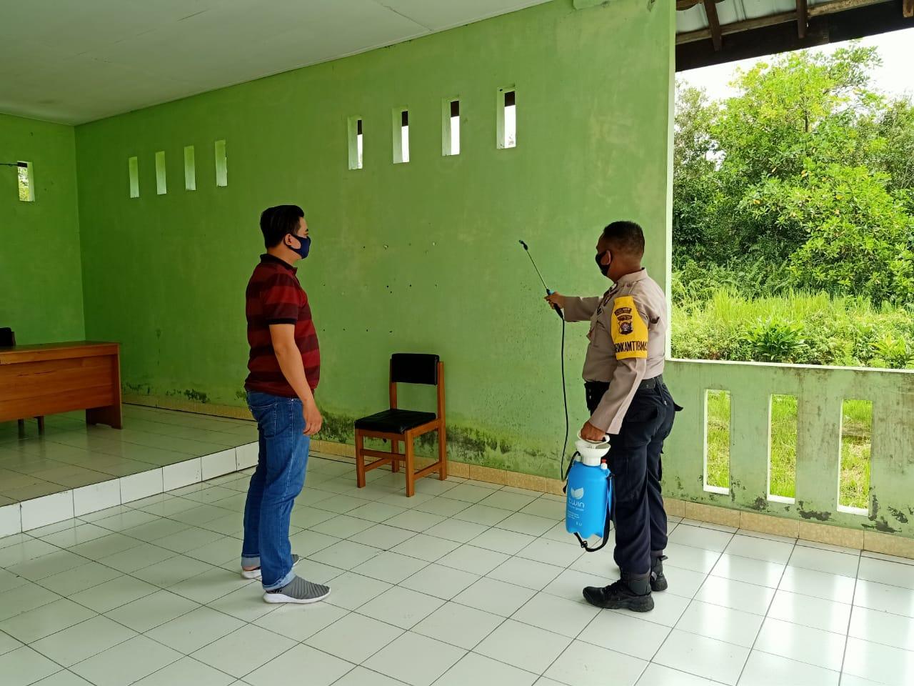 Putus Penularan Covid-19, Anggota Polsek Kahayan Tengah Semprot Desinfektan Pada Fasilitas Milik Desa